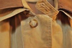 O botão superior em uma capa de chuva à moda Fotografia de Stock Royalty Free