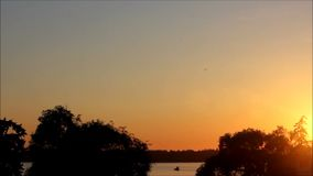O bote viaja através da água sob o por do sol vídeos de arquivo