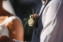 O boutonniere das rosas brancas, flor do noivo no revestimento do noivo fotografia de stock