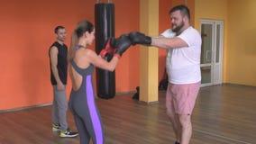 O boxe de treino de encaixotamento no treinamento para homens e as meninas sob a supervisão do artes marciais treinam, movimento  vídeos de arquivo
