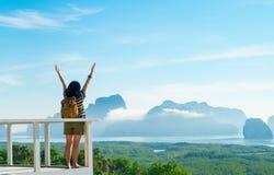 O braço aumentado da mulher do viajante mochileiro novo feliz até o céu aprecia Imagens de Stock Royalty Free