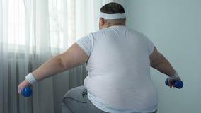 O braço de bombeamento masculino Unambitious muscles com pesos, estilo de vida sedentariamente, dieta vídeos de arquivo