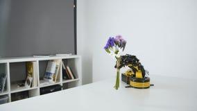 O braço do robô está dando a menina um ramalhete das flores Experiência com manipulador inteligente Modelo do robô industrial filme