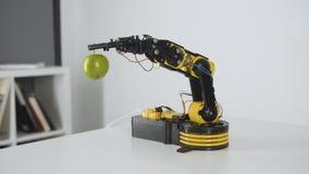 O braço do robô está dando a menina uma maçã Experiência com manipulador inteligente Modelo do robô industrial vídeos de arquivo