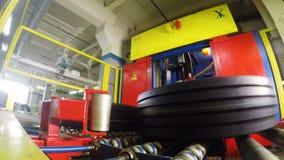 O braço do robô toma lugares do pneu no caso põe sobre o rolo vídeos de arquivo