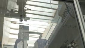 O braço mecânico automático do metal do close up opera-se e reflete-se filme