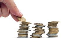 O braço põr uma moeda em uma pilha Foto de Stock