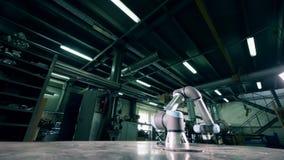 O braço robótico do metal funciona em uma fábrica em uma linha vídeos de arquivo