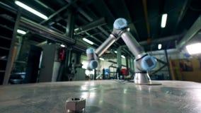 O braço robótico do metal move-se, trabalhando com uma engrenagem pequena filme