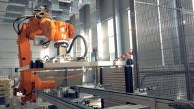 O braço robótico funciona na facilidade moderna da fábrica video estoque