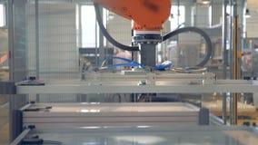 O braço robótico industrial moderno automatizado funciona na facilidade da fábrica video estoque