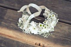 O bracelete com camomila floresce no assoalho de madeira Imagem de Stock