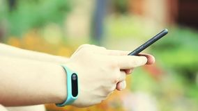 O bracelete de Smartphone equipa a metragem do jardim do verão da cópia das mãos video estoque