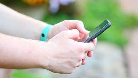 O bracelete de Smartphone equipa a metragem do jardim do verão da cópia das mãos filme