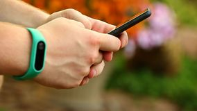 O bracelete de Smartphone equipa a metragem do jardim do verão da cópia das mãos vídeos de arquivo