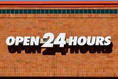 O branco abre 24 horas de signage contra o fundo do tijolo mim Fotografia de Stock