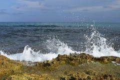 O branco acena o colisão com as rochas na costa Fotografia de Stock Royalty Free