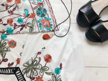 O branco bonito bordou o vestido, sandálias pretas e colar com a ágata no fundo de madeira branco Configuração lisa Foto móvel imagem de stock royalty free