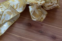O branco bonito e o Natal metálico do ouro curvam-se na tabela de madeira Fotografia de Stock Royalty Free