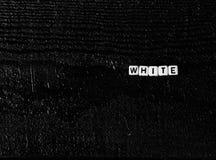 O ` branco do ` da palavra feito dos cubos em um fundo de madeira preto Fundo preto, Fotografia de Stock Royalty Free