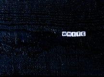 O ` branco do ` da palavra feito dos cubos em um fundo de madeira preto Fundo preto, Foto de Stock