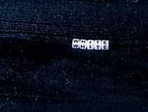 O ` branco do ` da palavra feito dos cubos em um fundo de madeira preto Fundo preto Foto de Stock Royalty Free