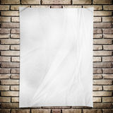 O branco do molde amarrotou o cartaz do retângulo na parede de tijolo do grunge fotografia de stock royalty free