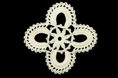 O branco fez crochê o doily do laço da pousa-copos no fundo preto Imagens de Stock