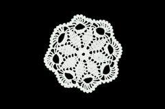 O branco fez crochê o doily do laço da pousa-copos no fundo preto Fotografia de Stock Royalty Free