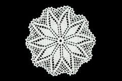 O branco fez crochê o doily do laço da pousa-copos no fundo preto Imagem de Stock Royalty Free