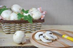 O branco fresco cresce rapidamente cogumelo na cesta marrom no fundo de madeira Vista superior Copie o espaço Fotos de Stock
