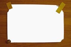 O branco isolou a folha de papel em uma superfície de madeira Imagem de Stock