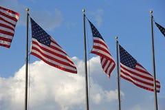 O branco patriótico das bandeiras do Estados Unidos nubla-se o céu azul Fotografia de Stock Royalty Free