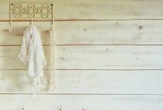 O branco peroliza a colar e o lenço do laço que penduram na parede de madeira Vintage filtrado Foco seletivo Imagem de Stock Royalty Free
