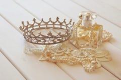 O branco peroliza a colar, a tiara do diamante e a garrafa de perfume Fotos de Stock Royalty Free