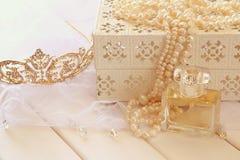 O branco peroliza a colar, a tiara do diamante e a garrafa de perfume Fotografia de Stock Royalty Free