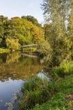 O branco pintou a ponte de madeira refletida em um rio pequeno Fotografia de Stock Royalty Free
