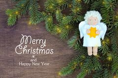 O branco sentiu o anjo do Natal com amarelo protagonizar nas mãos aos ramos naturais frescos do abeto vermelho da árvore de Natal ilustração do vetor