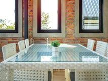 O branco tece cadeiras e a tabela de vidro na parede de tijolo e no vidro de janela fotografia de stock royalty free