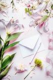 O branco vazio envolve com lápis e vários equipamento e flores da decoração no fundo pálido cor-de-rosa da tabela, vista superior Imagens de Stock Royalty Free