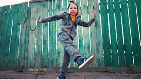 O breakdancer novo dança no fundo da cerca de madeira verde velha filme