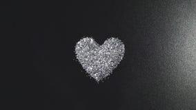 O brilho de prata arranja à forma do coração no fundo preto com luz do voo video estoque