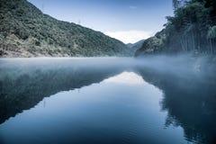O brilho do sol nas árvores verdes está no monte, em uma reflexão no lago calmo com névoa, no céu azul e nas nuvens brancas Tom f imagem de stock