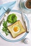 O brinde fritado com enchimento, abacate cor-de-rosa e rúcula do ovo sae da sagacidade Imagens de Stock Royalty Free