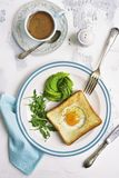 O brinde fritado com enchimento, abacate cor-de-rosa e rúcula do ovo sae da sagacidade Imagem de Stock