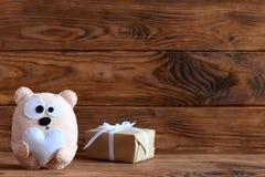 O brinquedo bonito do urso de feltro guarda o coração, caixa de presente feito a mão no papel do ofício no fundo de madeira marro Imagem de Stock Royalty Free