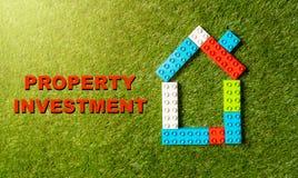 O brinquedo colorido obstrui o investimento da propriedade da casa e do texto escrito na grama no negócio do mercado imobiliário fotos de stock