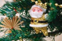 O brinquedo de Santa Claus está pendurando em uma árvore de Natal fotos de stock royalty free