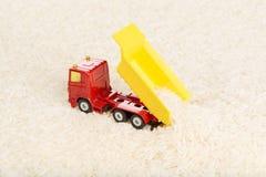 O brinquedo do caminhão basculante descarrega grões do arroz Imagem de Stock