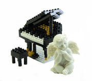 O brinquedo do piano feito do brinquedo plástico obstrui a estátua do cupido Imagem de Stock Royalty Free